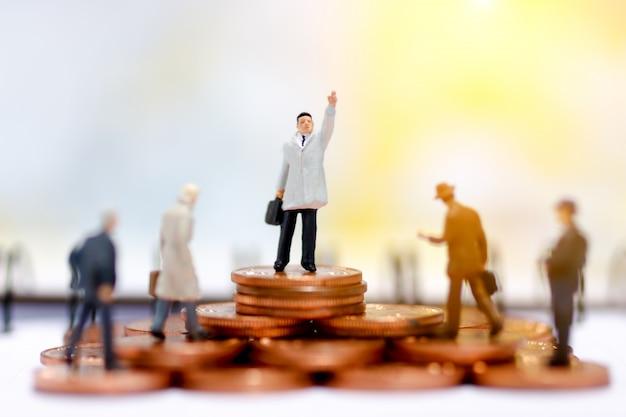 Gente de negocios en miniatura de pie en el paso del dinero de la moneda