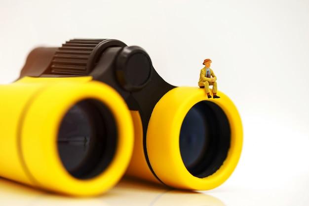 Gente de negocios en miniatura que se sienta encima de binoculares para encontrar personas para trabajar