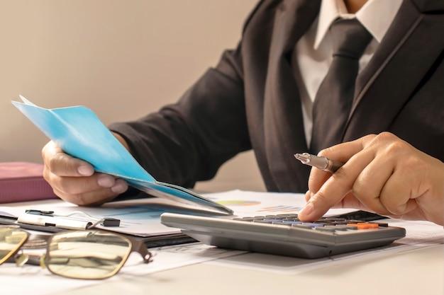 Gente de negocios o contadores que están revisando documentos financieros y libros de cuentas, trabajo e ideas financieras.