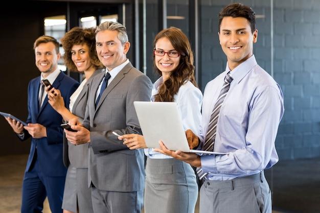 Gente de negocios de pie en una fila y con teléfono móvil, ordenador portátil y tableta digital en la oficina