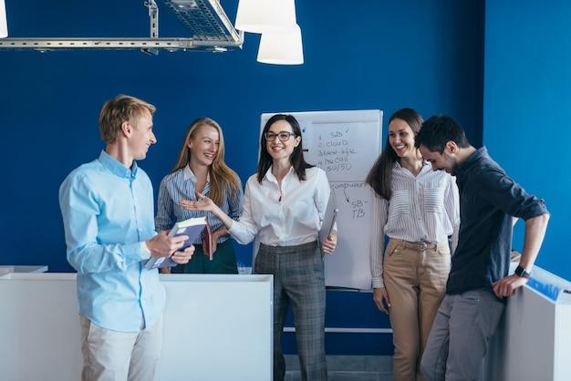 Gente de negocios de pie juntos en una oficina.