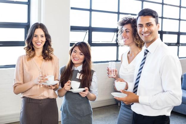 Gente de negocios de pie y juntos y sonriendo en la oficina