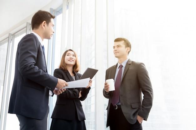 Gente de negocios de pie en el pasillo del edificio de oficinas hablando durante el descanso para tomar café
