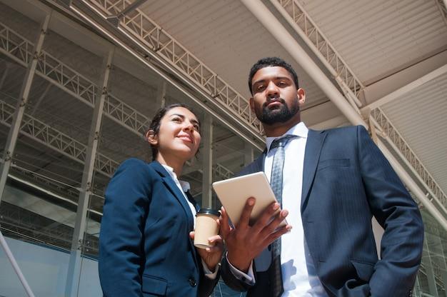 Gente de negocios posando, sosteniendo la tableta y la bebida al aire libre