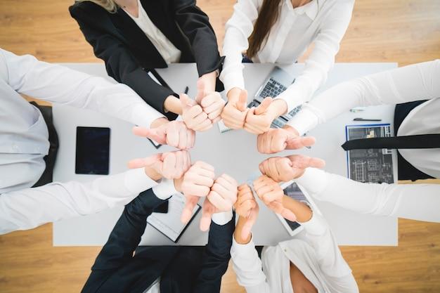 La gente de negocios pulgar hacia arriba en el fondo del escritorio. vista desde arriba