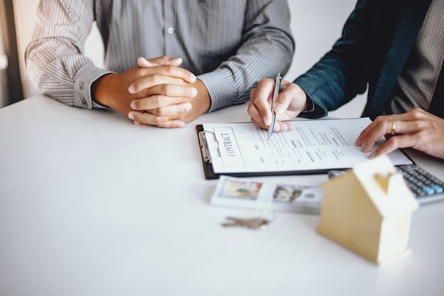Gente de negocios que firma contrato haciendo un trato con el agente inmobiliario. concepto de consultor y concepto de seguro de hogar.