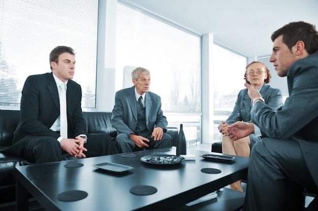 Gente de negocios que tiene un descanso en la reunión de la oficina