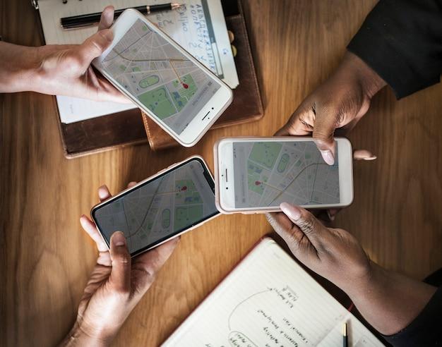 Gente de negocios que usa mapas en teléfonos