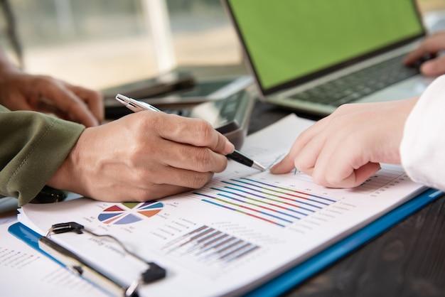 Gente de negocios reunida en la oficina escribiendo notas en notas adhesivas.