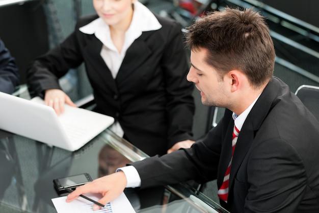 Gente de negocios: reunión de equipo en una oficina con computadora portátil