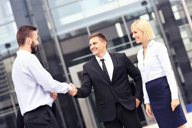 Gente de negocios saludando fuera del edificio moderno