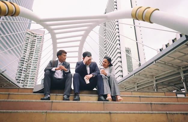 Gente de negocios sentado en el paso discutiendo juntos
