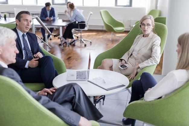 Gente de negocios sentados juntos en sillones en el pasillo de la oficina y tener una discusión