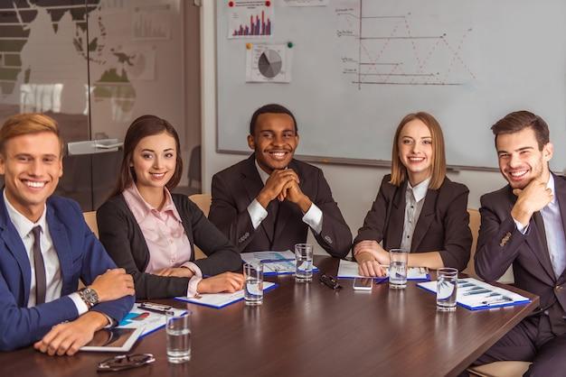 La gente de negocios se sienta en la mesa y sonríe.