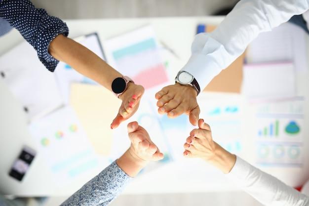 La gente de negocios sobre la mesa de trabajo saludan las manos.