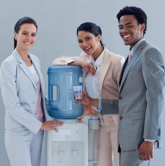 Gente de negocios sonriente con un enfriador de agua en la oficina