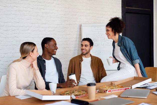 Gente de negocios sonriente con plano medio de pizza