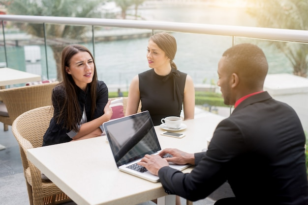 Gente de negocios sonriente que tiene una reunión al aire libre. lluvia de ideas exitosa.