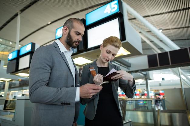 Gente de negocios con tarjeta de embarque y uso de teléfono móvil