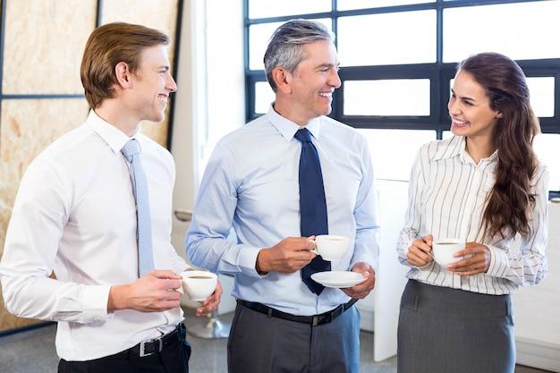 Gente de negocios tomando té e interactuando durante el recreo en la oficina