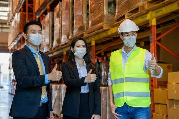 Gente de negocios con trabajadores de almacén con cascos de pie en el pasillo entre estantes altos con productos envasados, trabajadores de almacén en almacén con gerentes.