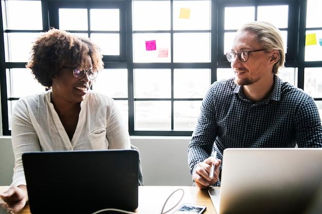 Gente de negocios trabajando en computadoras portátiles durante una reunión