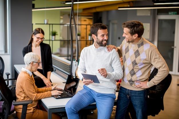 Gente de negocios trabajando y comunicándose mientras están de pie en la oficina junto con colegas sentados en el fondo