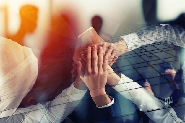 Gente de negocios uniendo sus manos en el concepto de oficina de trabajo en equipo y asociación doble exposición