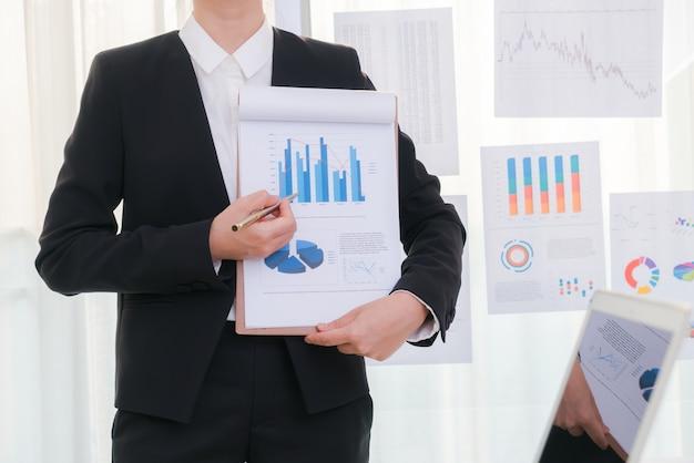 La gente de negocios usando la computadora portátil y cartas financieras en la reunión o