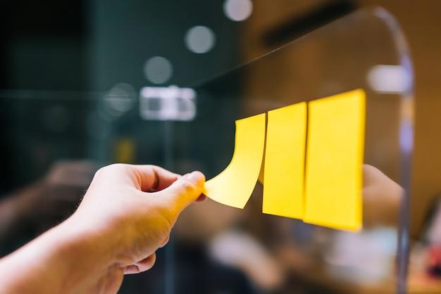 Gente de negocios usando una nota adhesiva en el separador de plexiglás para compartir ideas