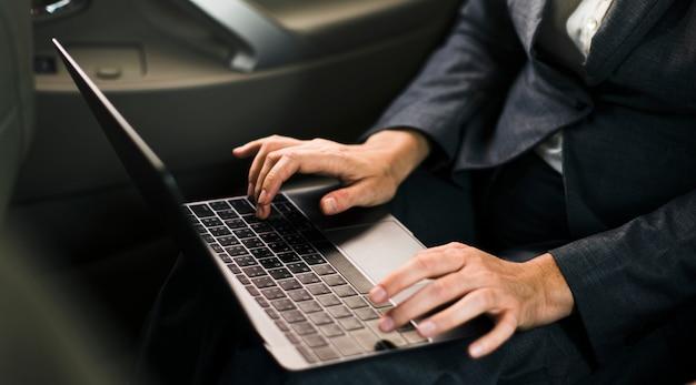 Gente de negocios usando una red de computadoras portátiles dentro de un automóvil