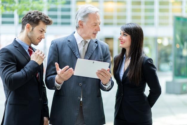 Gente de negocios usando una tableta al aire libre