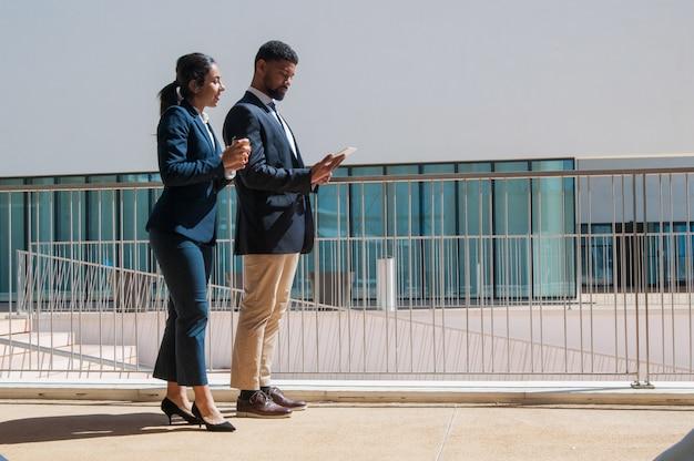 Gente de negocios usando tableta y de pie al aire libre