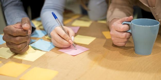 Gente en la oficina escribiendo ideas en notas adhesivas