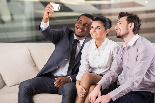 La gente en la oficina durante el receso está haciendo selfie.