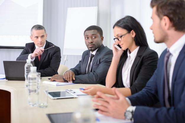 La gente en la oficina está sentada a la mesa y discutiendo.