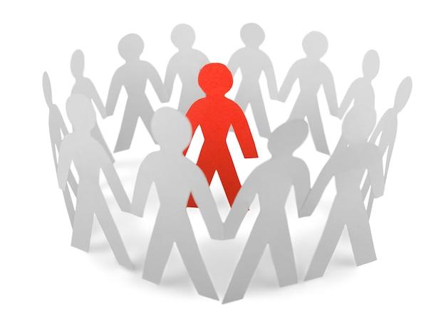 Gente de papel de pie en un círculo y un hombre de papel rojo dentro