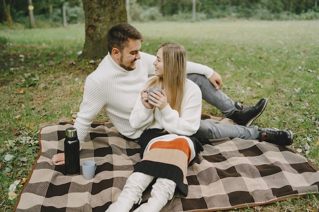 Gente en un parque. mujer con un abrigo marrón. hombre con un suéter blanco. pareja en un picnic.