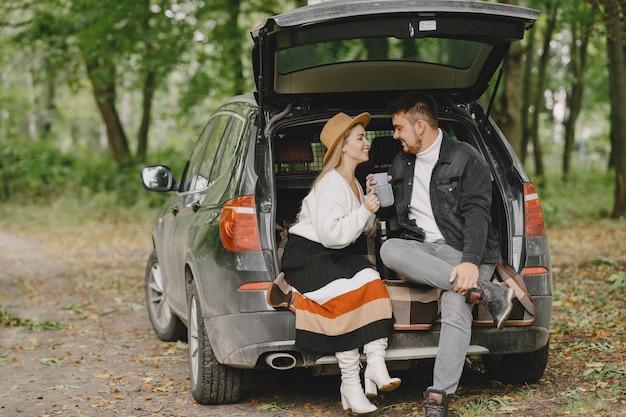 Gente en un parque. mujer con un suéter blanco. personas en el maletero de un coche.