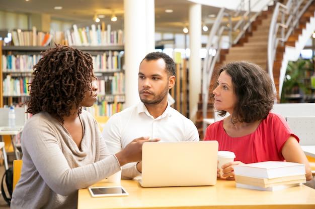 Gente pensativa hablando mientras usa la computadora portátil en la biblioteca