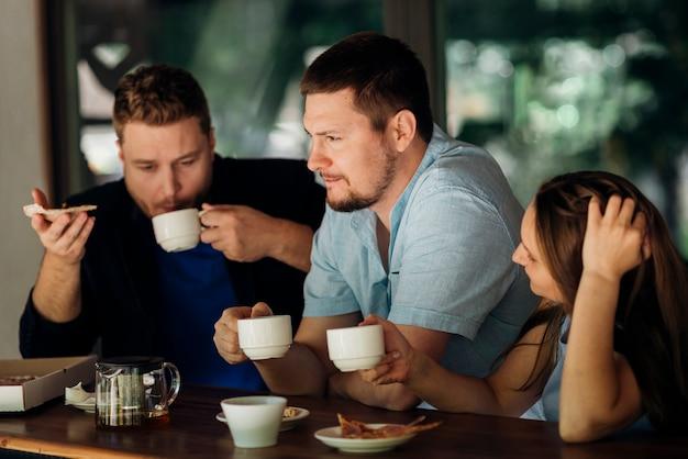 Gente pensativa tomando café y comiendo pizza en la cafetería
