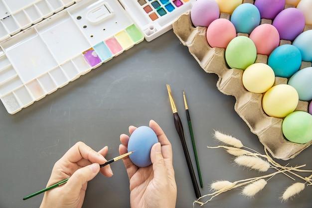 Gente pintando coloridos huevos de pascua - concepto de celebración de vacaciones de semana santa