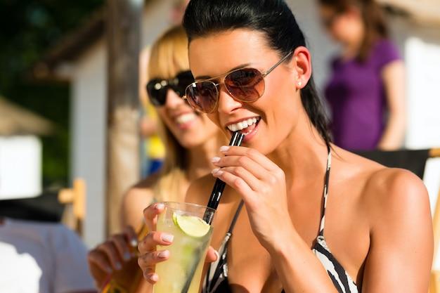 Gente en la playa bebiendo una fiesta