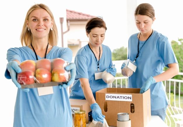 Gente preparando cajas para donar para el día de la comida