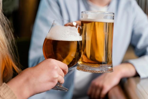 Gente de primer plano sosteniendo jarras de cerveza