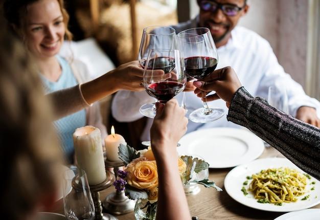 Gente que se aferra copas de vino juntas en restaurante