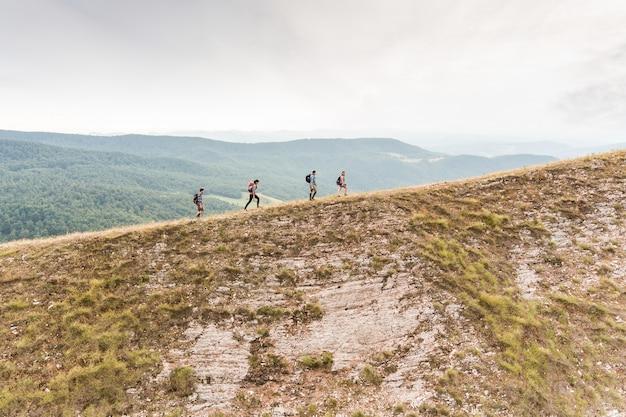 Gente que camina en el borde superior de la montaña