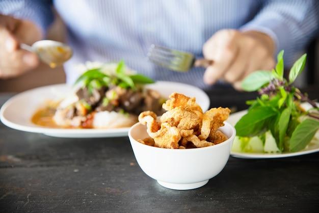 Gente que come el conjunto de fideos de estilo del norte de tailandia picante - concepto de comida tailandesa
