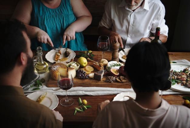 Gente que disfruta de una idea de la receta de la fotografía del alimento de la tabla del queso