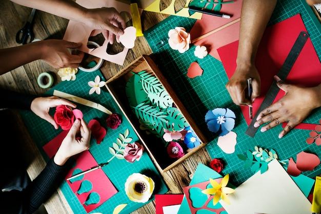 Gente que hace las flores de papel arte de la artesanía trabajo artesanal